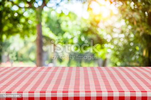 1048926386 istock photo Backgrounds: Red and white checkered tablecloth with green lush foliage at background 1048841982