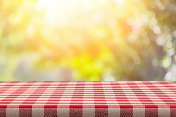 Hintergrund: Rot-weiß karierte Tischdecke mit gelbem üppigem Laub im Hintergrund – Foto