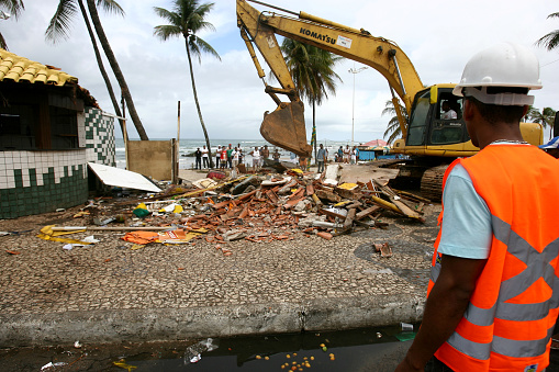 salvador, bahia, brazil - july 15, 2014: Reotro-excavator machine makes demolition of kiosk on the sidewalk of Itapua beach in Salvador. The demolition is part of the site's requalification work carried out by the city hall.