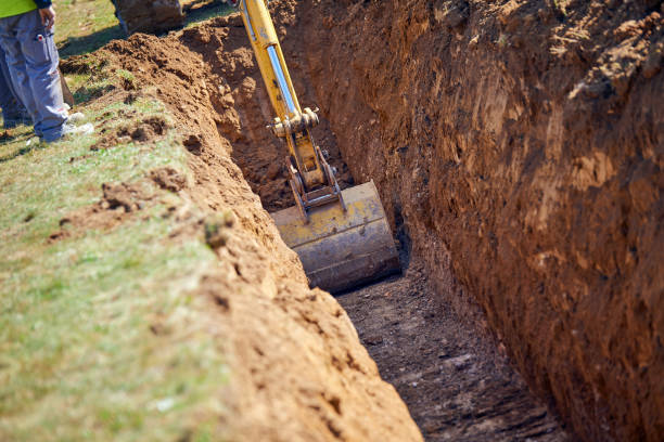 Backhoe - Digging a Trench Excavator digs the foundation for water pipes shovel stock pictures, royalty-free photos & images