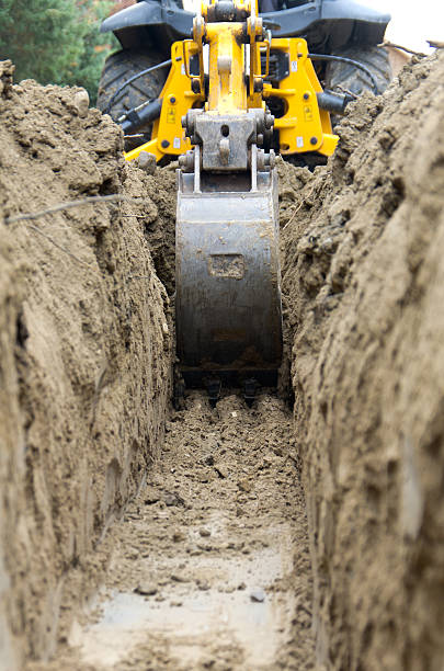 backhoe digging a trench - greppel stockfoto's en -beelden