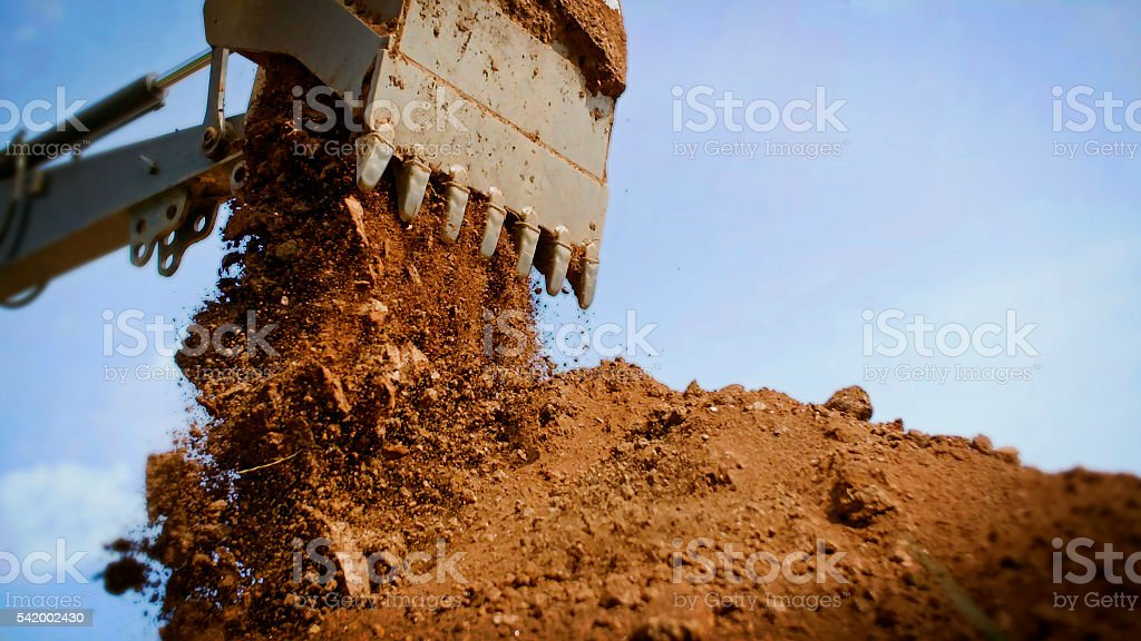 Backhoe emptying bucket full of dirt. stock photo