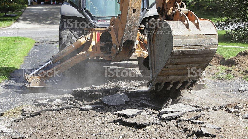 Backhoe Excavator Demolishing Old Residential Driveway stock photo