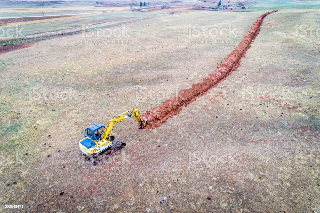 backhoe excavator digging a ditch stock photo