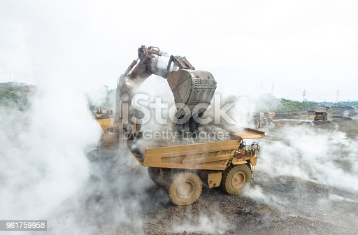 Backhoe load Hot and smokey foggy material into mining dump truck in Nickel Mining in South Sulawesi, Indonesia.