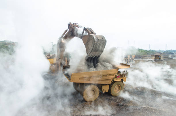 backhoe load hot material into mining dump truck - nickel stock photos and pictures