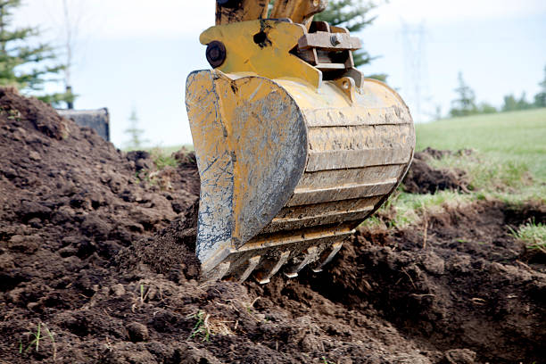 Backhoe A Backhoe Digging a Trench shovel stock pictures, royalty-free photos & images