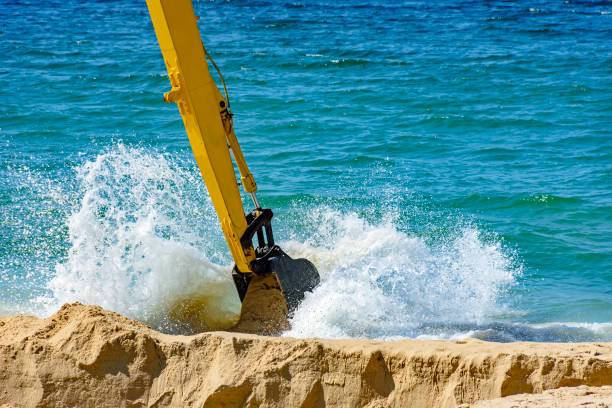 Backhoe removing sand from the beach and playing in the sea with water spray stock photo