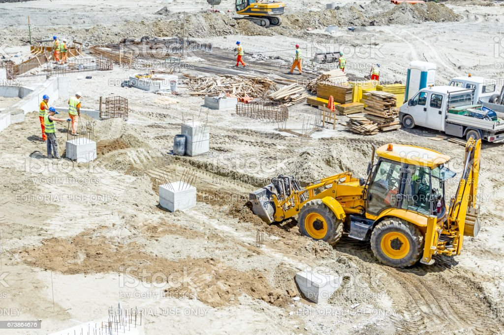 Backhoe tractor is leveling sand at construction site stock photo