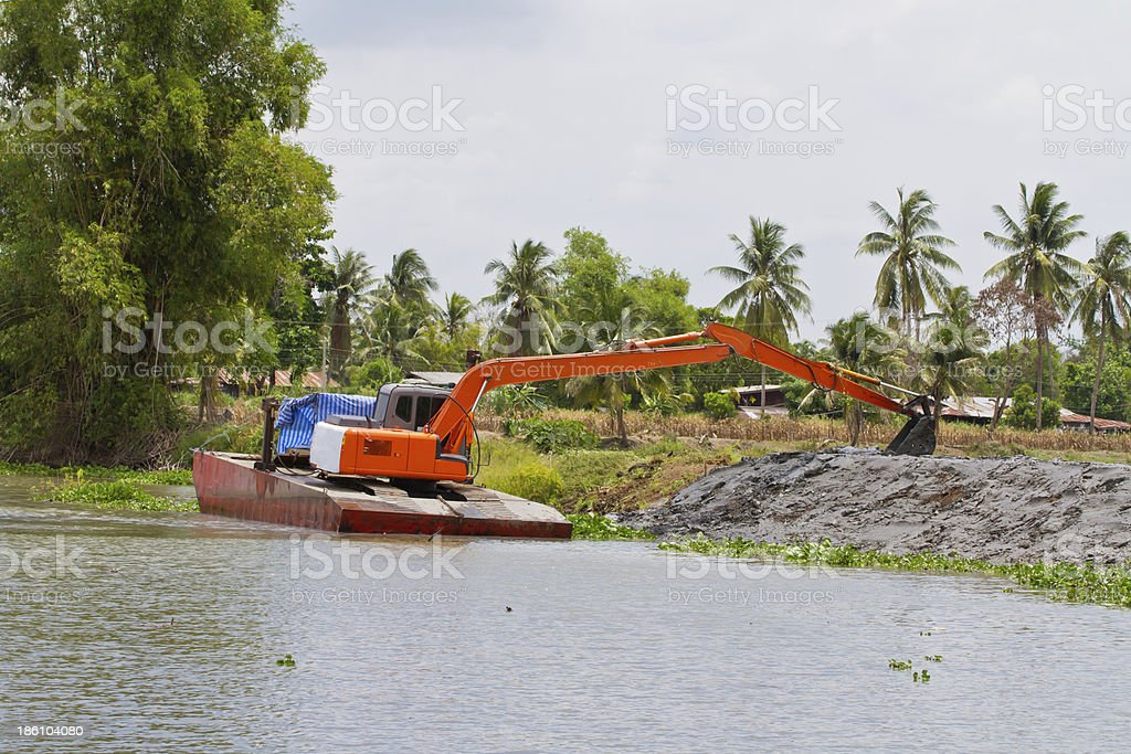 Backhoe tractor on pontoon, working in the canal royalty-free stock photo