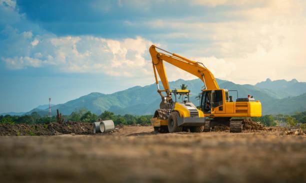 backhoe werken op de weg bouwplaats, met bergen en lucht achtergrond. - graven stockfoto's en -beelden