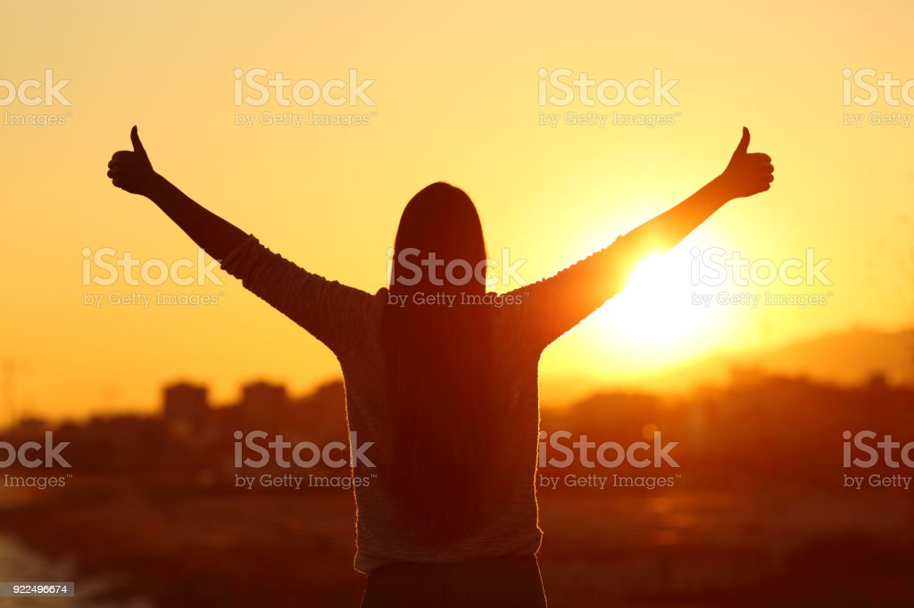 Backlight of a woman raising arms with thumbs up stock photo