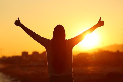 Backlight Of A Woman Raising Arms With Thumbs Up - zdjęcia stockowe i więcej obrazów Dobra wiadomość
