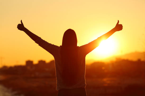 Backlight of a woman raising arms with thumbs up Back view backlight silhouette of a woman raising arms with thumbs up to the sun at sunset positive emotion stock pictures, royalty-free photos & images