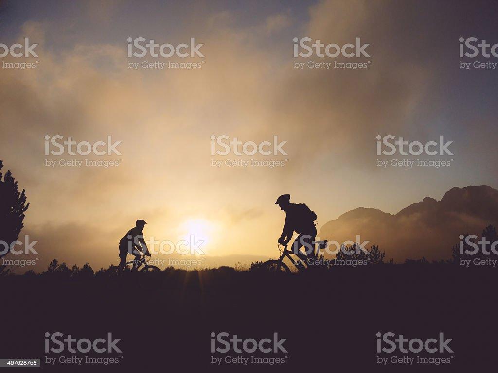 Retroiluminación de ciclistas de al atardecer. - foto de stock