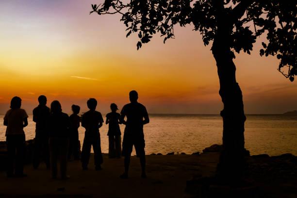 backlight shot of group of people looking at sunset - традиционная церемония стоковые фото и изображения