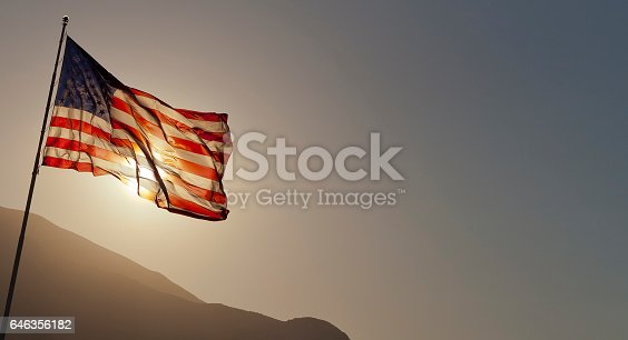 579407234 istock photo Back-lit American flag flying on pole with copy space. 646356182
