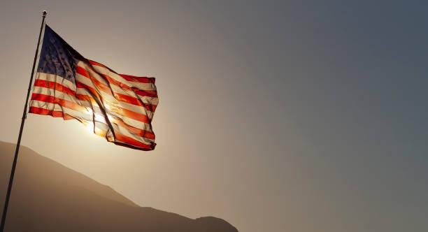 Back-lit American flag flying on pole with copy space. stock photo