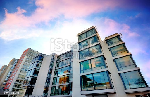 istock Backlit apartment building against dramatic sky 185108679