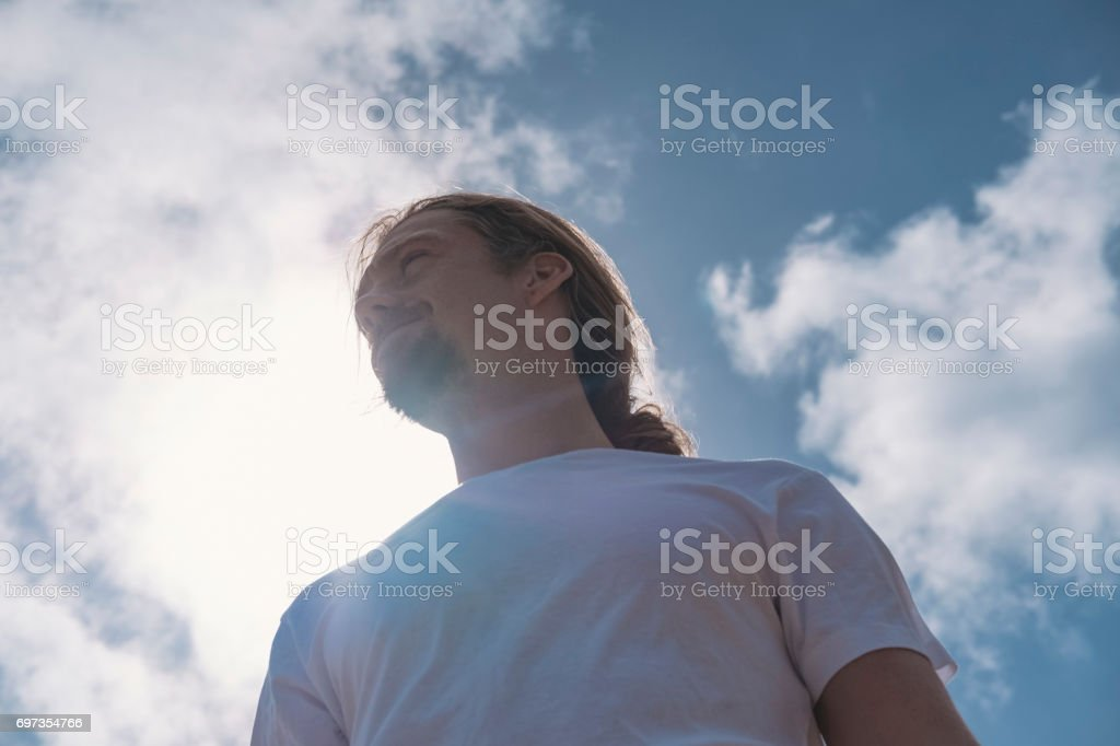 Backlit Candid Male Portraits against summer sunshine and blue sky. stock photo