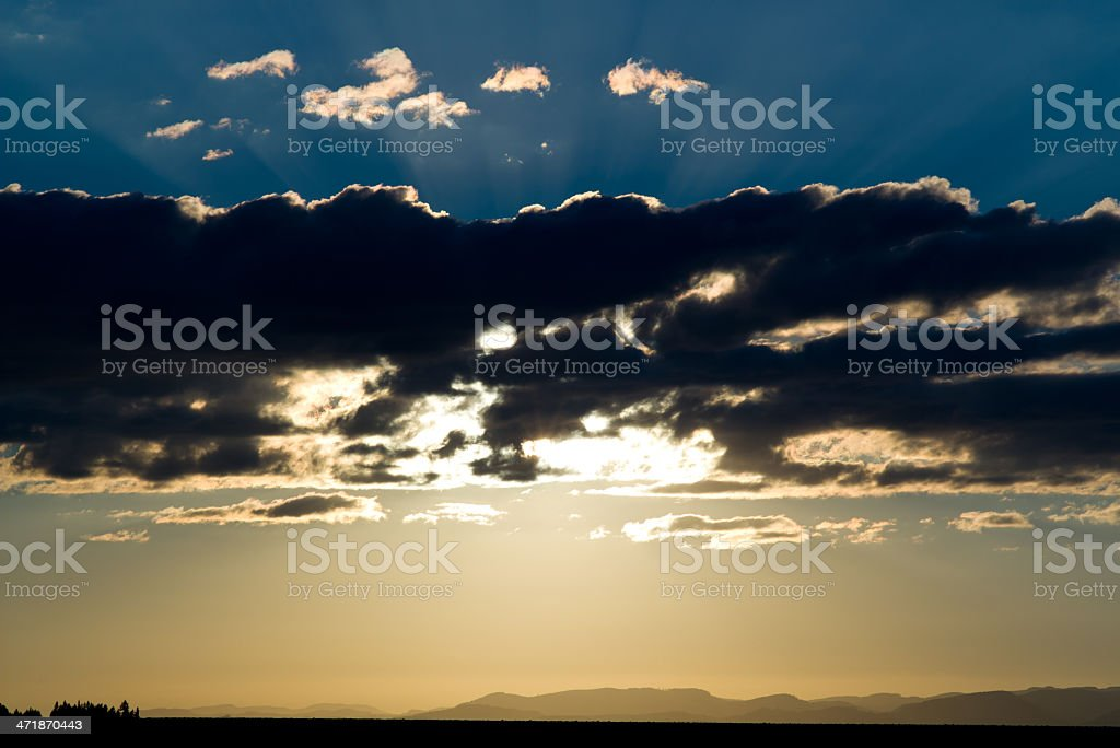 Backlit clouds at sunset over mountains royalty-free stock photo