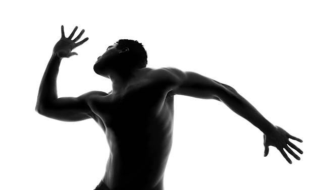 Backlit dancer A beautifully lit backlit shirtless male torso showing movement and dance shirtless male models stock pictures, royalty-free photos & images