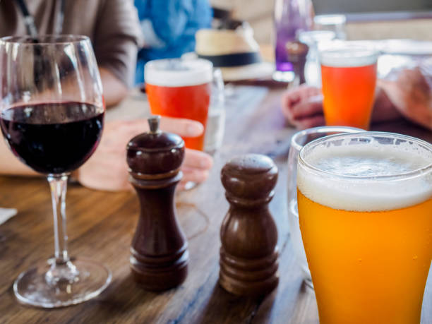 Backlit glasses of beers and a red wine on a dinning table stock photo