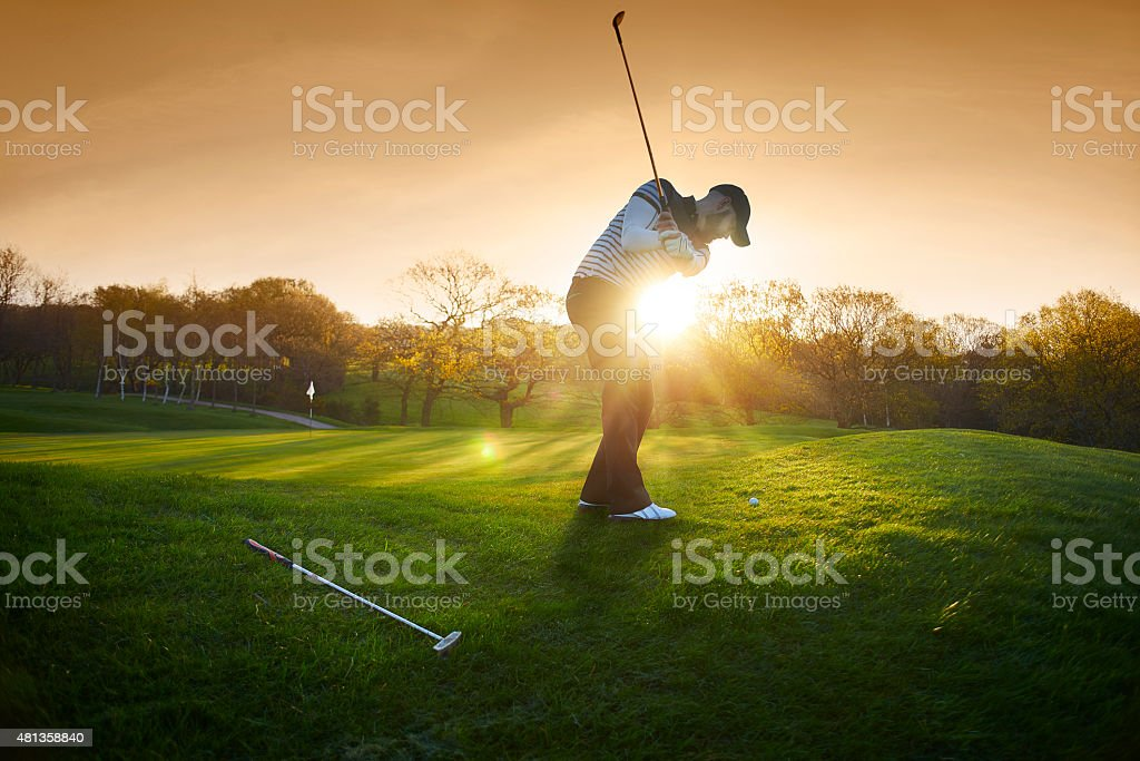 backlit golf course with golfer chipping onto green stock photo
