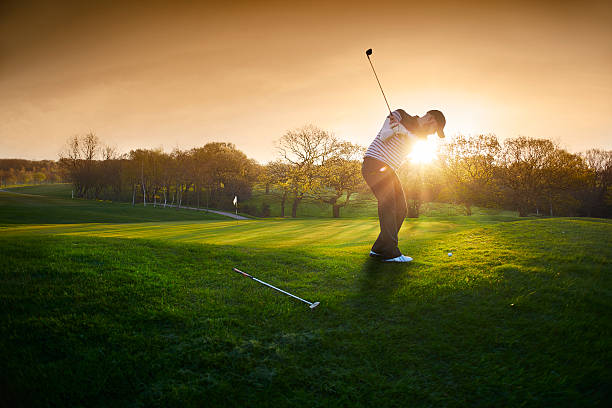 backlit golf course with golfer chipping onto green - golf stock photos and pictures