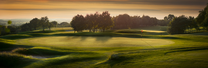 a panoramic scene of an empty golf course , with the shadows falling toward camera as the light fades .
