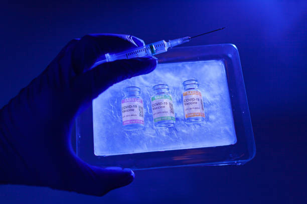 Back-lit hand with surgical glove in close-up holding ice-pack with inside vials of COVID-19 vaccine stored at low temperature. Labeled SARS-CoV-2 against Coronavirus stock photo