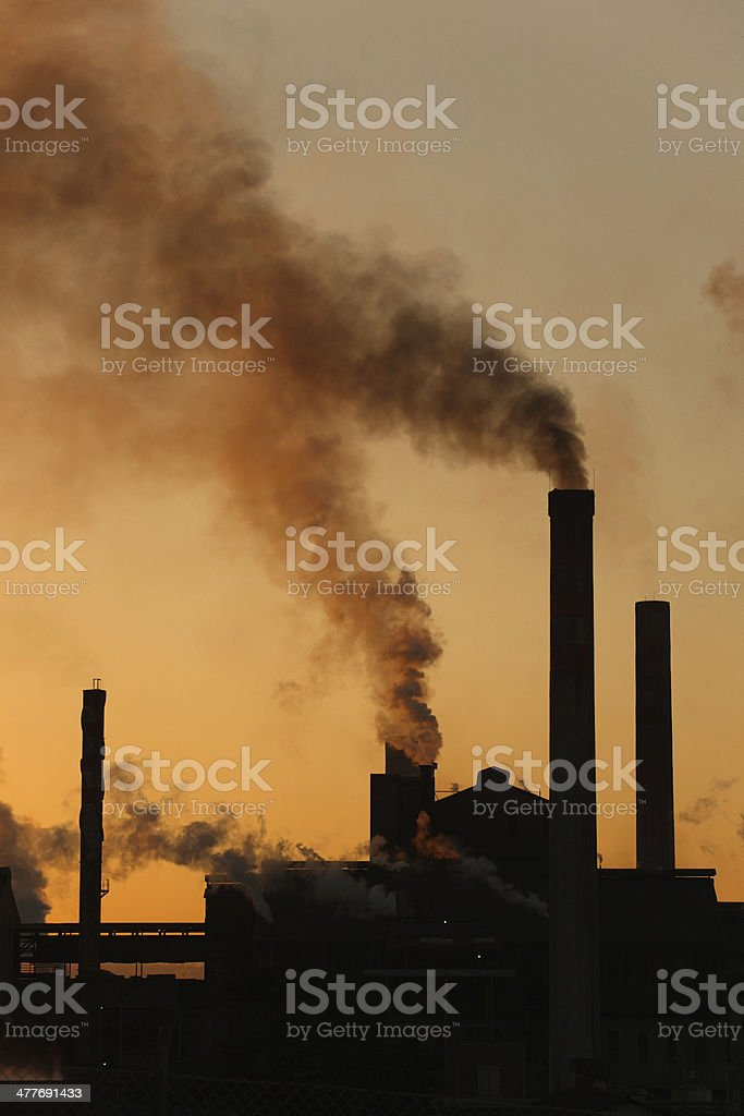 Backlit industrial chimney stacks factory dark smoke pollution rising upwards stock photo