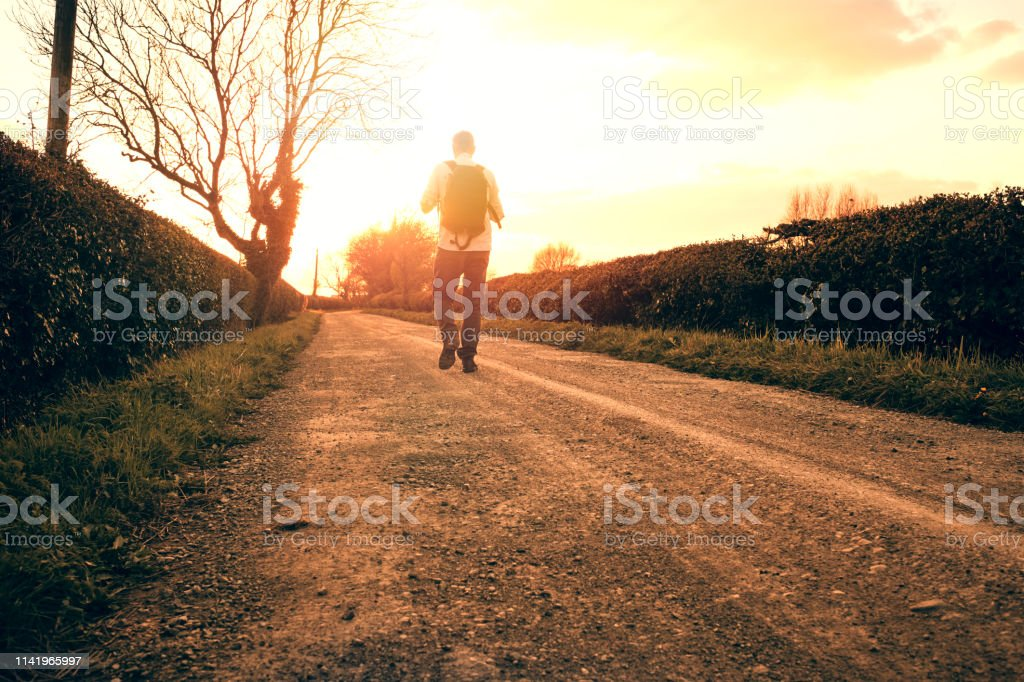 Backlit man walking along a country road in golden sunset sunshine. stock photo