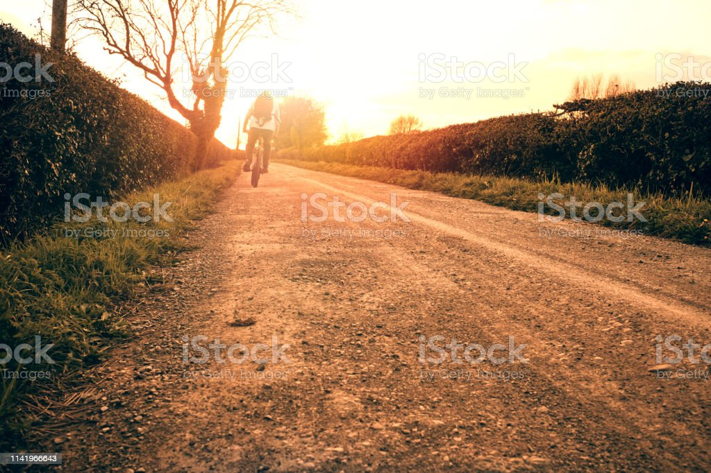 Backlit Motion blurred man cycling along a country road at sunset. stock photo