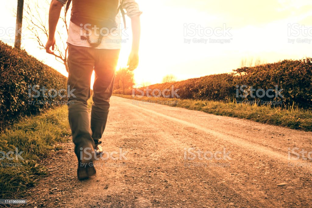 Backlit motion blurred man walking along a country road in golden sunset sunshine. stock photo