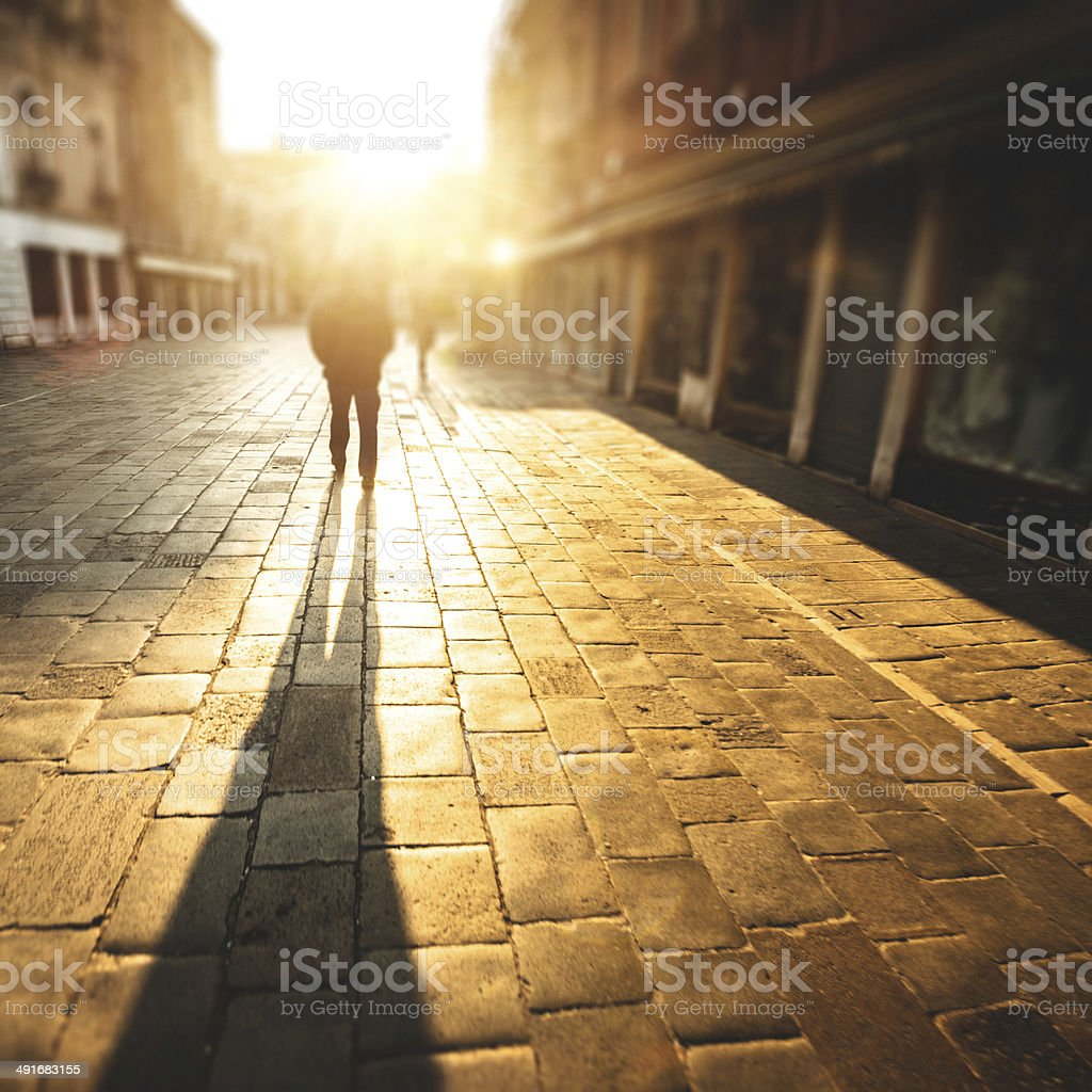 backlit of man walking on the cobblestone stock photo