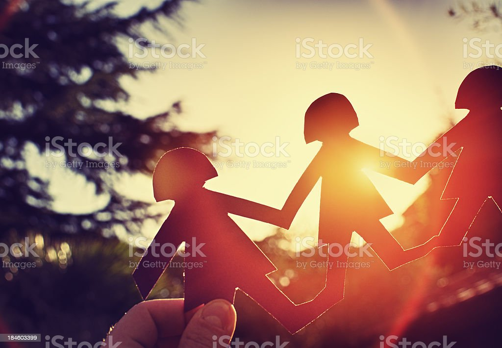 Backlit paper cut-out community at dusk stock photo