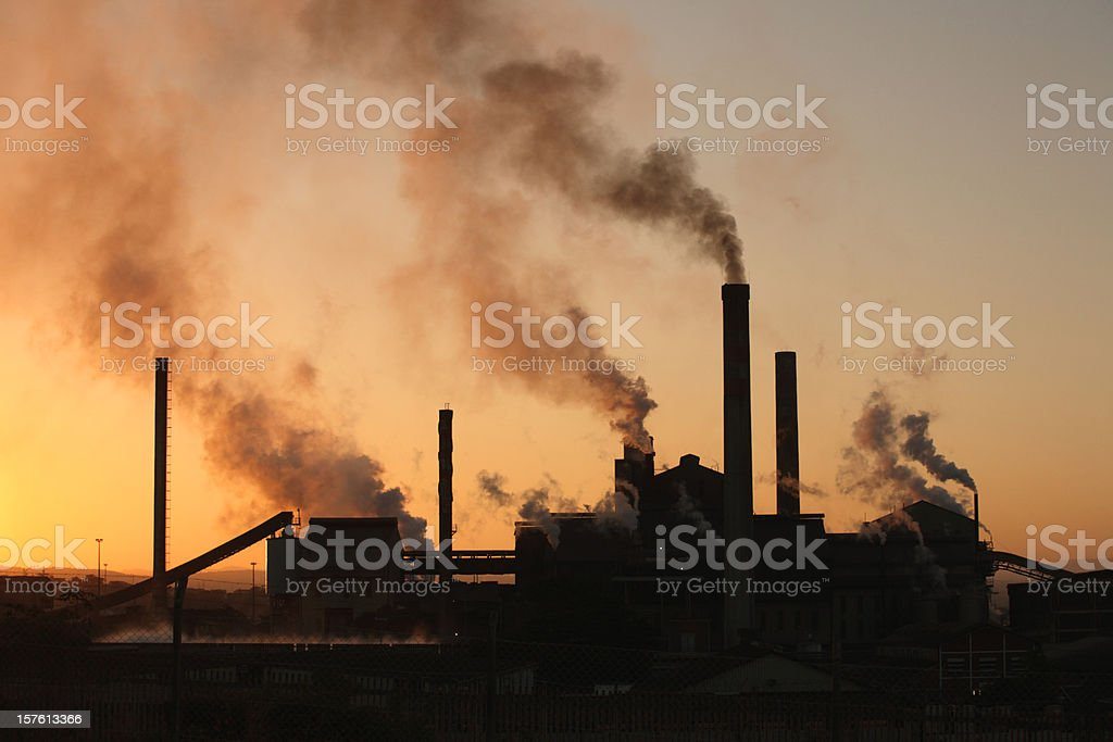 Backlit paper mill factory sunset with dark smoke rising upwards stock photo