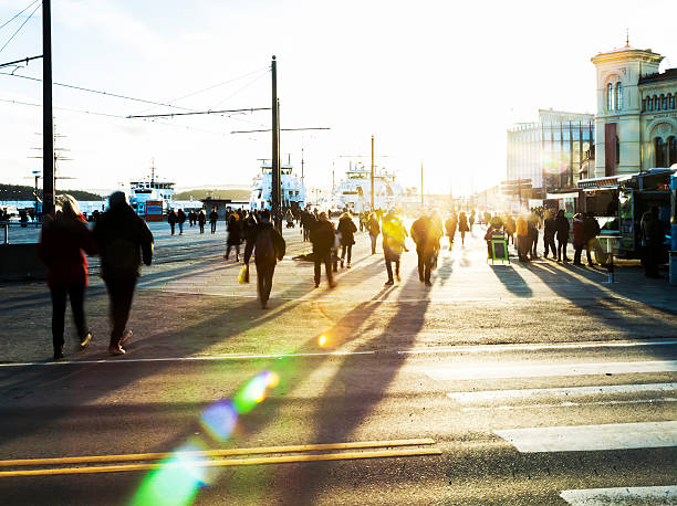 Backlit people  walking in the street at sunset. Silhouettes of backlit people  walking  to catch the ferry for Nesodden at sunset .  Aker Brygge, Oslo, Norway. oslo stock pictures, royalty-free photos & images