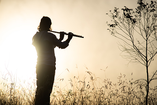 a piper playing a c flute against a hard sun in the background amidst a country setting