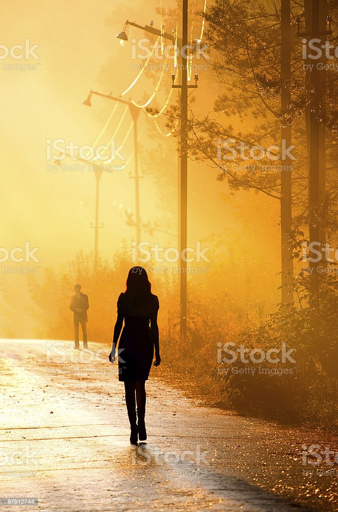 Backlit portrait of a woman walking towards a man at sunset royalty-free stock photo