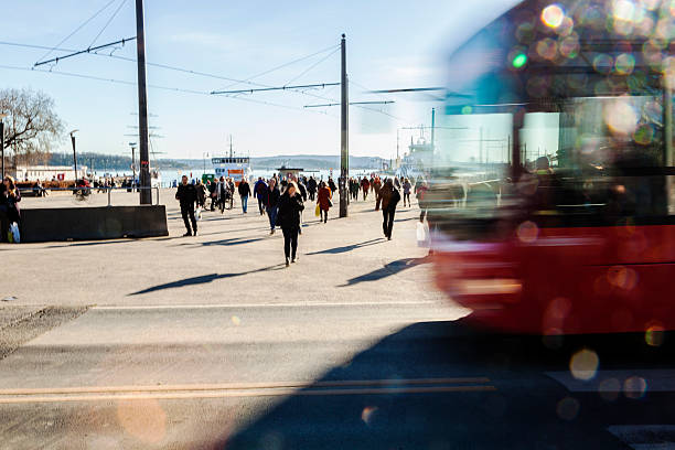 Backlit  red bus and people  walking in the street. Silhouettes of backlit,   blurred  bus with bokeh lights  in the street and  people  walking  to catch the ferry for Nesodden.  Aker Brygge, Oslo, Norway. oslo stock pictures, royalty-free photos & images