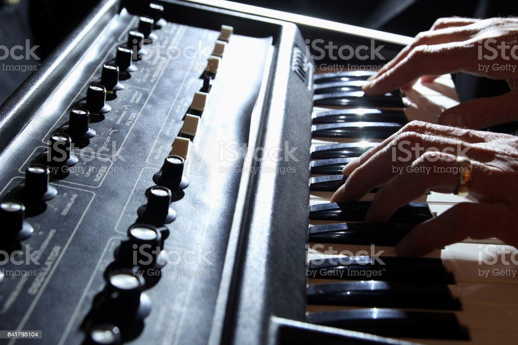 Backlit shallow focus shot of man playing 1970s synth keyboard stock photo