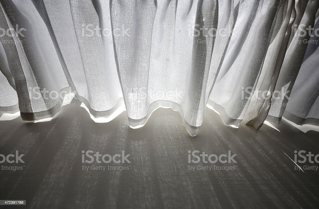 Backlit White Curtains with Shadows on a Window Sill stock photo