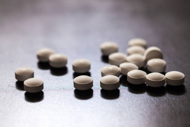 Backlit white pills - Opioid and prescription medication addiction epidemic or crisis - concept - foto stock