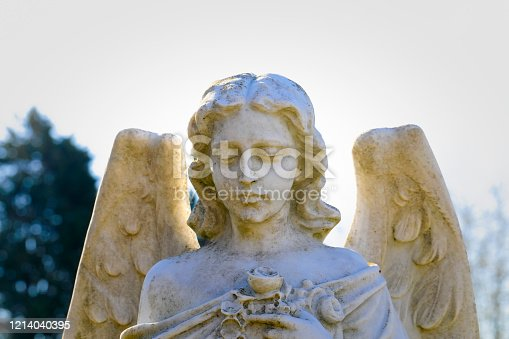 This winged white angel, photographed with strong back lighting, is carrying roses. Merton, Surrey, UK.