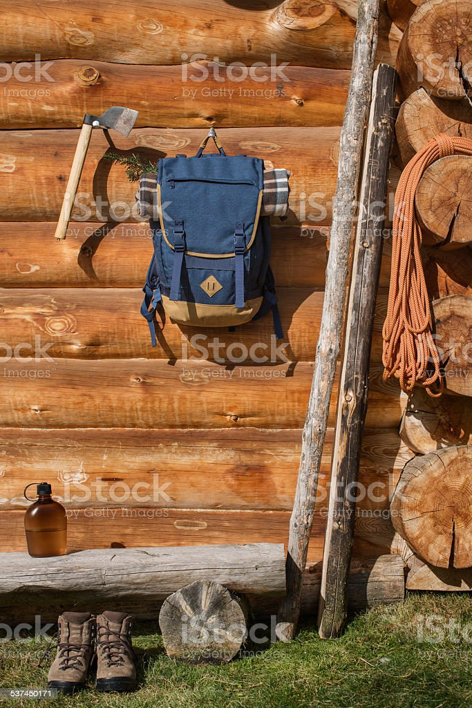 Backpack and axe hanging outside cabin stock photo