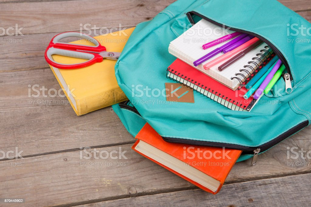 Backpack and school supplies: books, notepad, felt-tip pens, scissors on brown wooden table stock photo