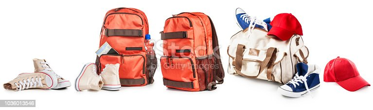 Backpack and bag with sport shoes and baseball cap collection isolated on white background. Tourism, sport and healthy lifestyle concept