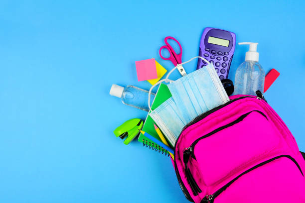 Backpack full of school supplies and COVID 19 prevention items. Top view, spilling onto a blue background. Back to school during pandemic concept. stock photo